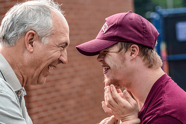 A male Carer laughing with a young man he is caring for – for the Donate and Donation pages