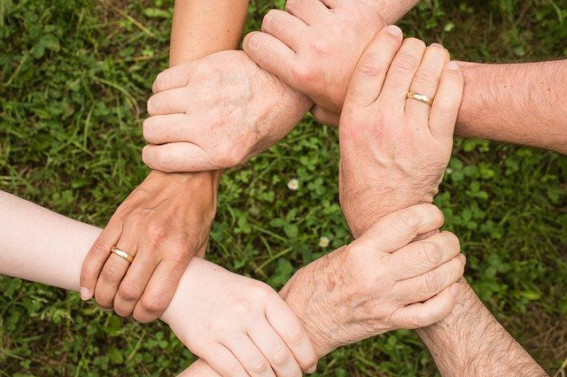 6 hands interlinking and working as a team