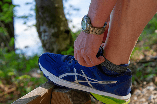 Person tying their running shoe