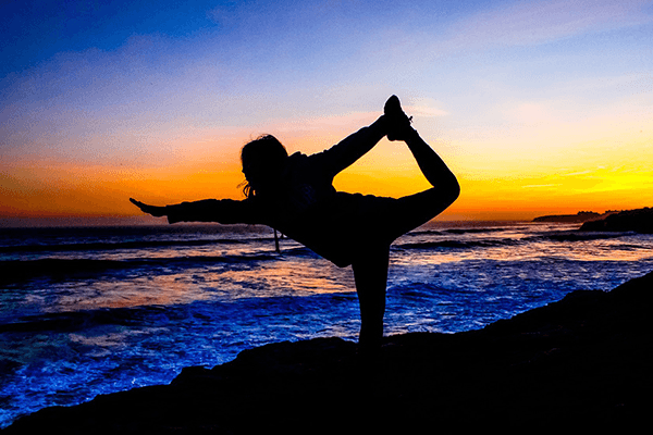 Women in yoga pose in front to the ocean at dusk